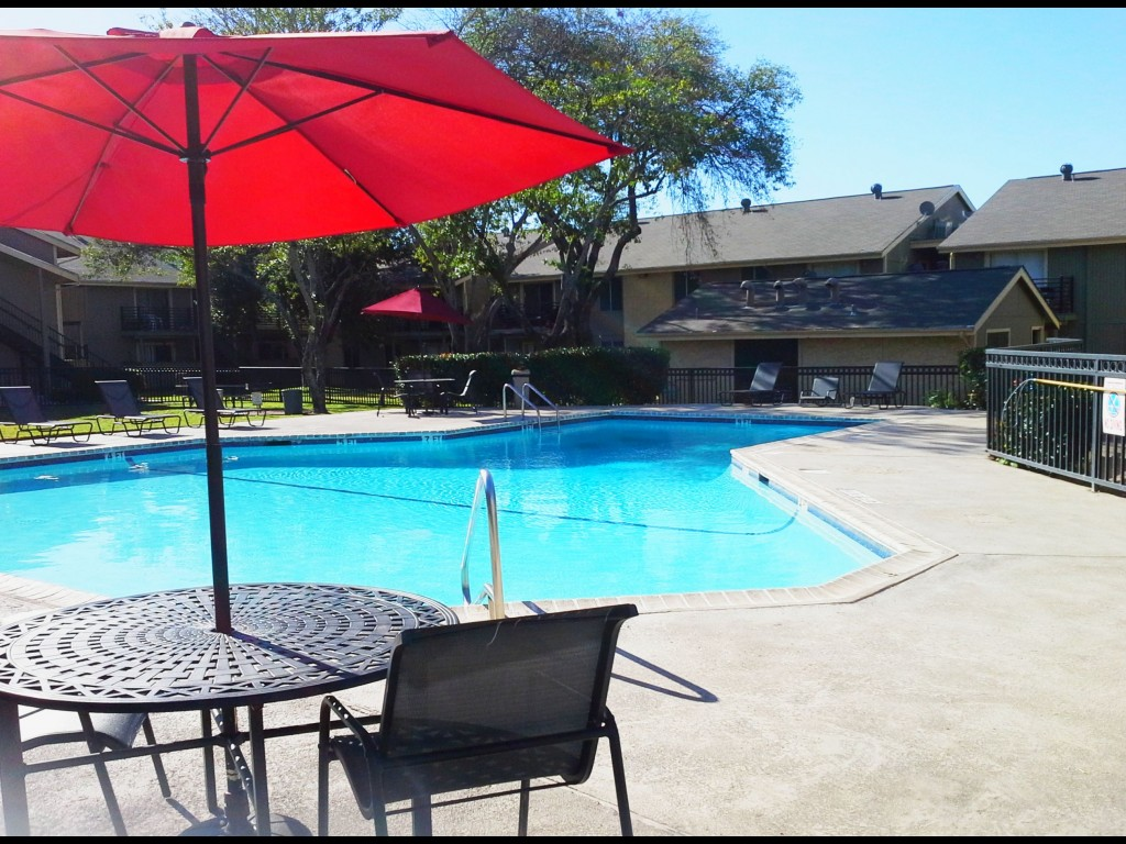 Pool Patio Furniture with Umbrella at Aubry Hills Apartments in Austin, TX