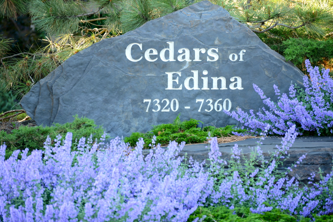 Property Sign with Flowers at Cedars of Edina Apartments in Edina, MN