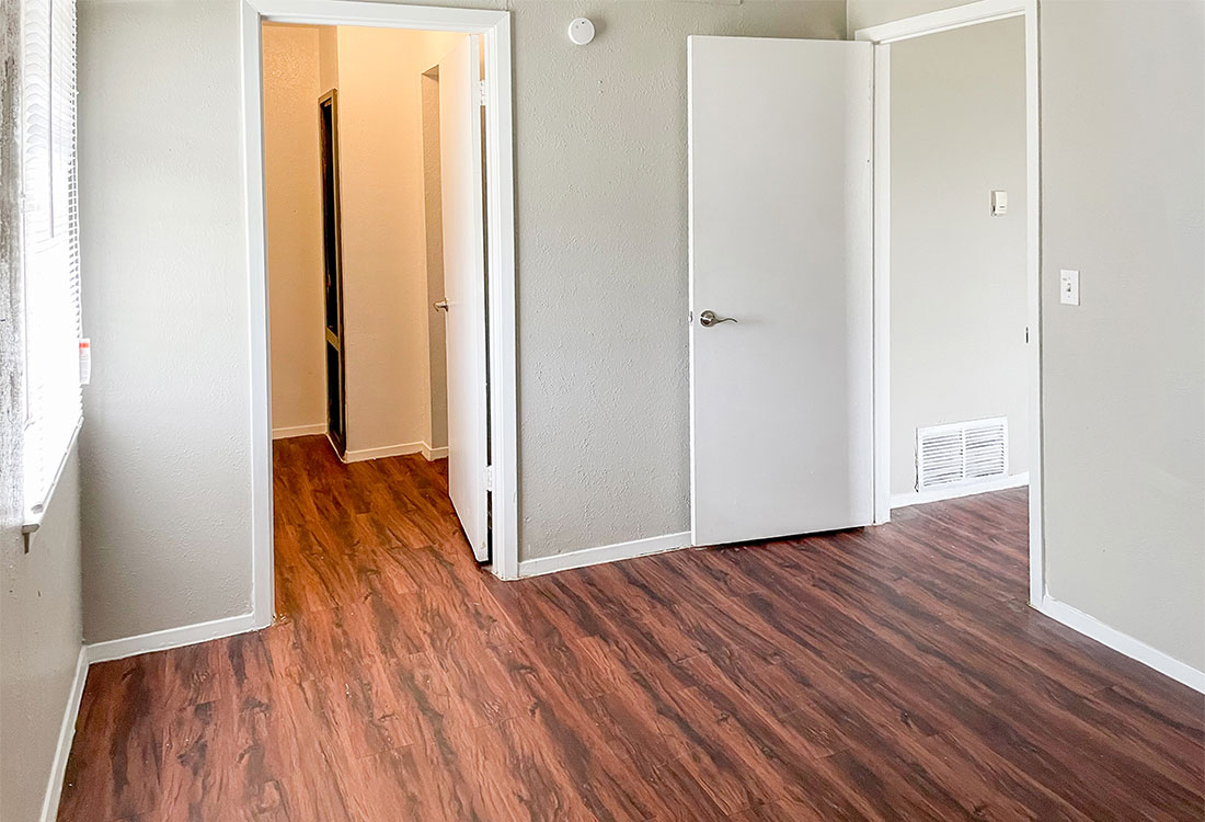 Bedrooms with Plank Flooring at Courtyard Park Apartments in Abilene, TX