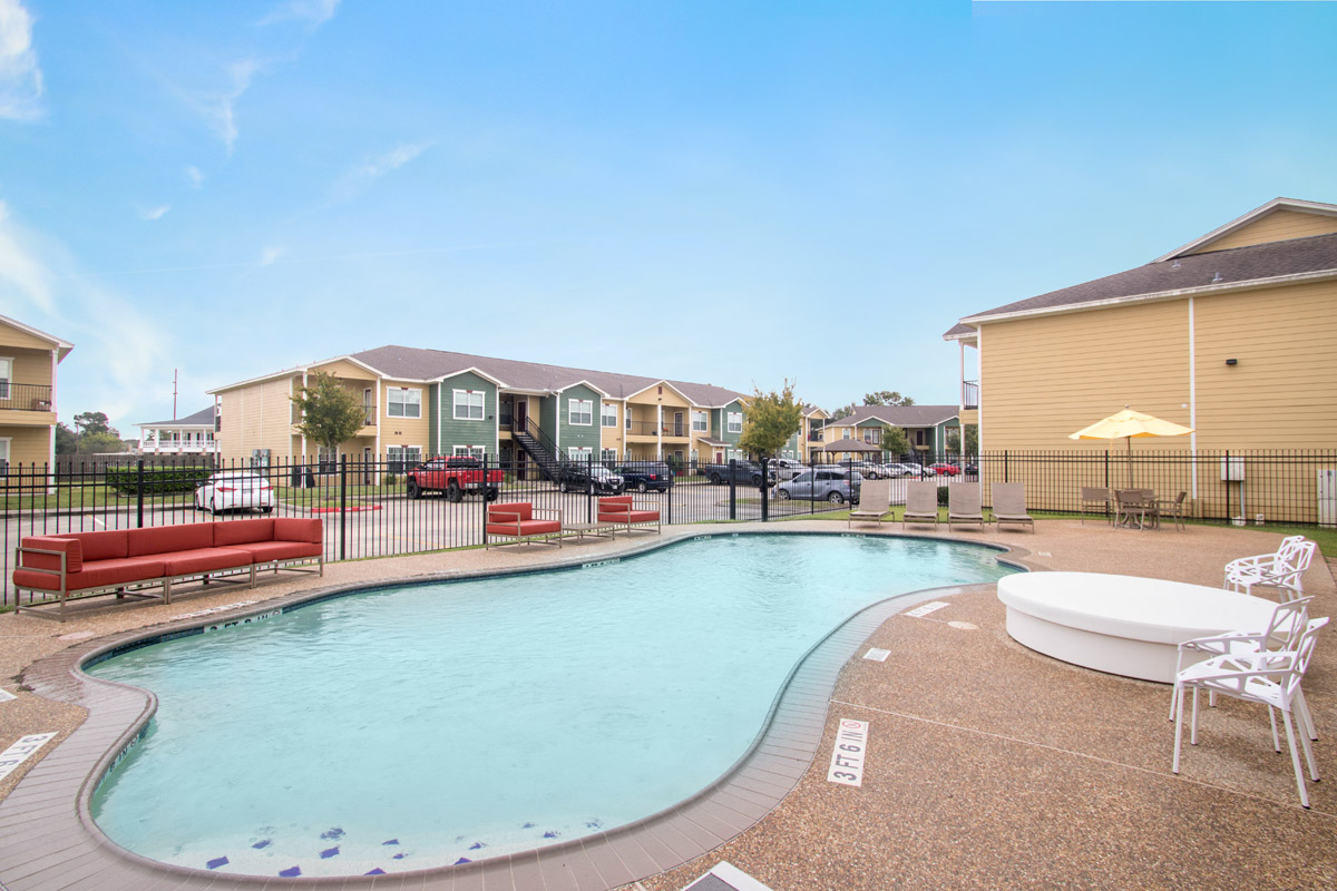Outdoor Swimming Pool Seating at Cypress Bend Village Apartments in Beaumont, TX