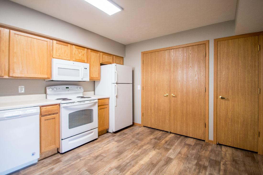 Spacious Kitchen with White Appliances and Utility Closet