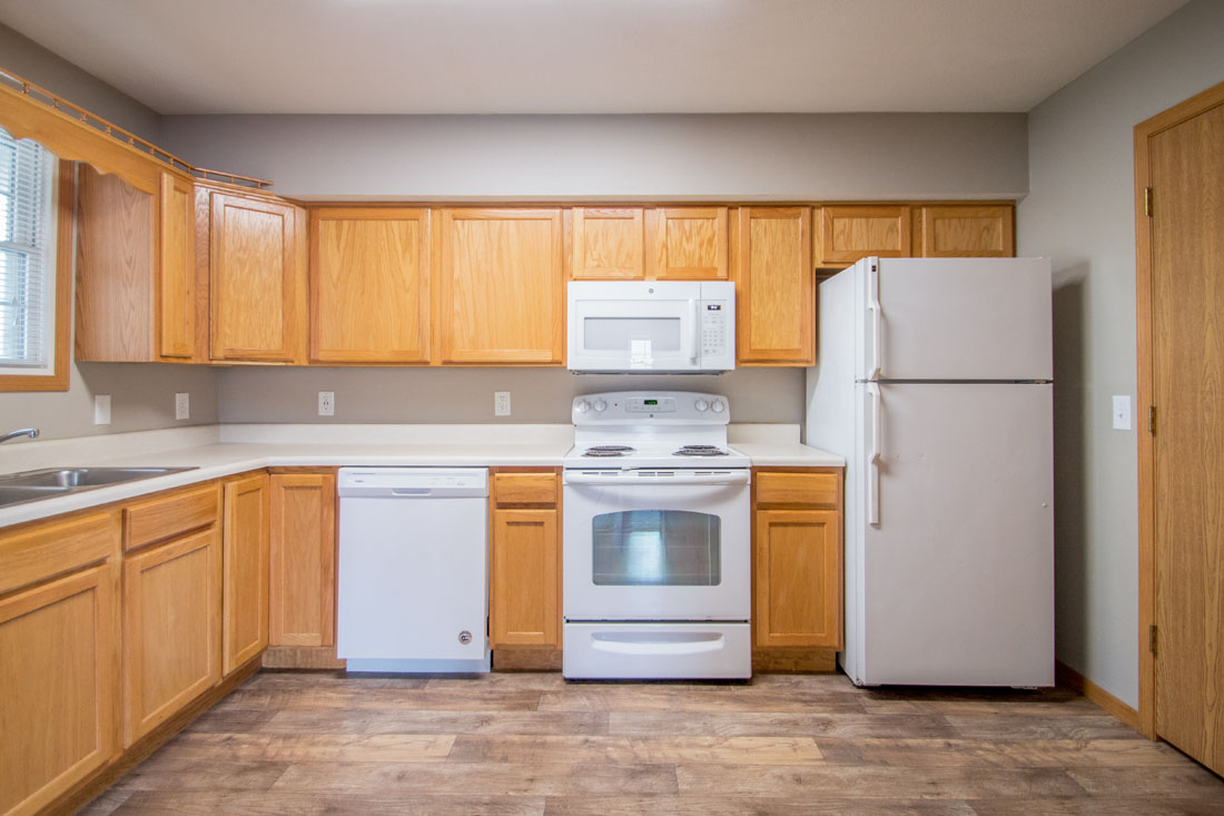 Spacious Kitchen with White Appliances and Wood-Look Flooring