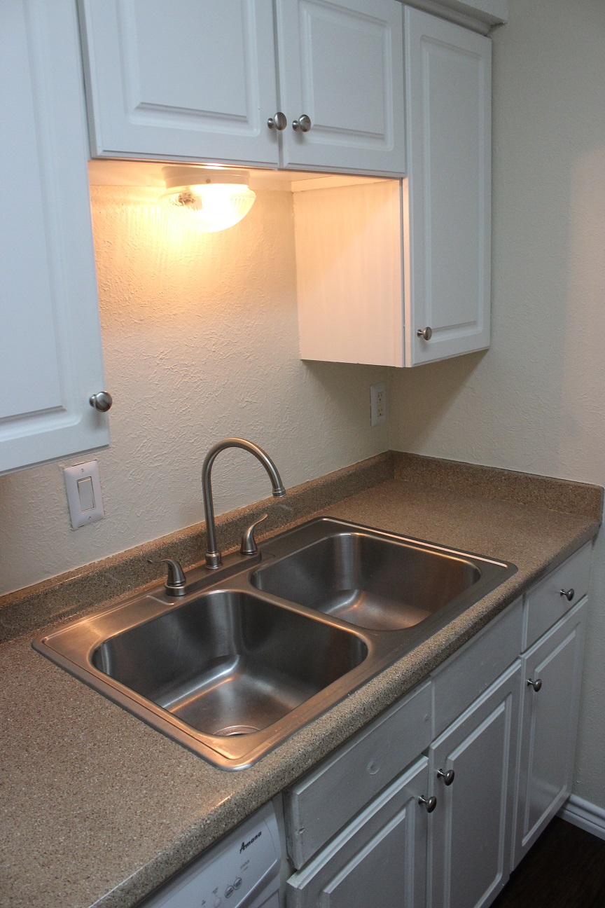 White Wooden Cabinetry at The Avanti on Central Apartments in Bedford, TX