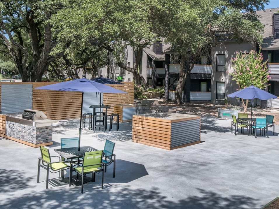 Patio Enclosure with Grills and Tables at The Henry B Apartments in San Antonio, TX