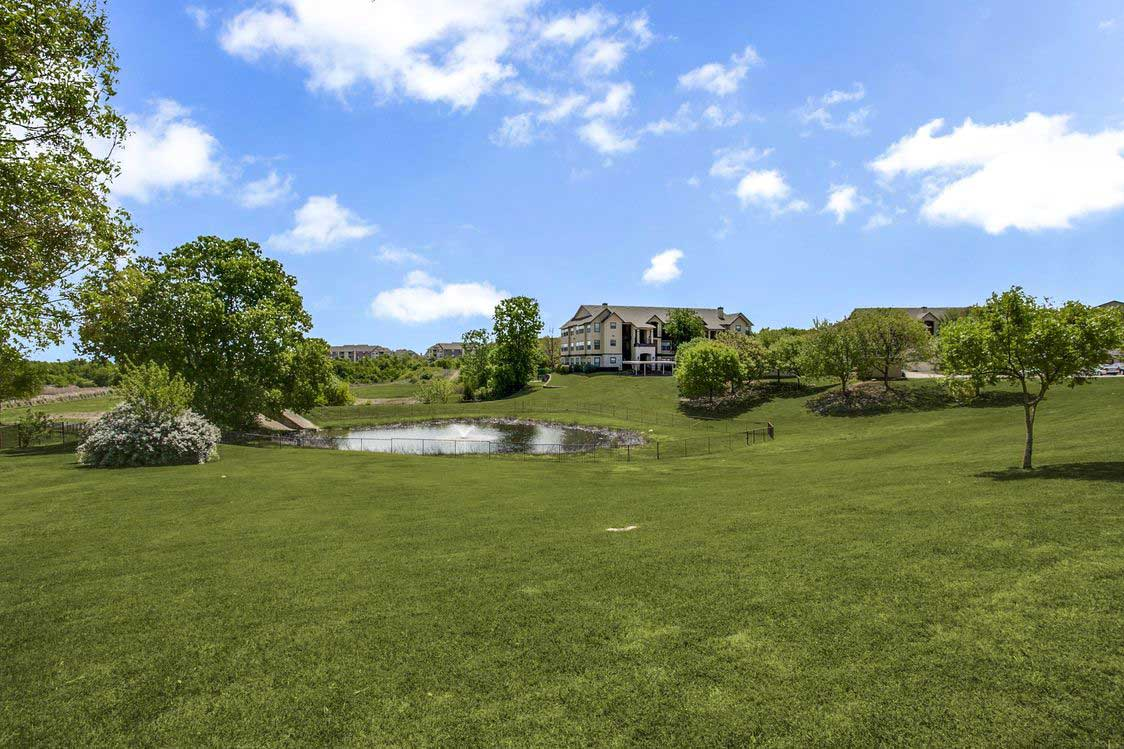 Lush Landscaping with Pond at Hidden Lakes Apartments in Haltom City, Texas