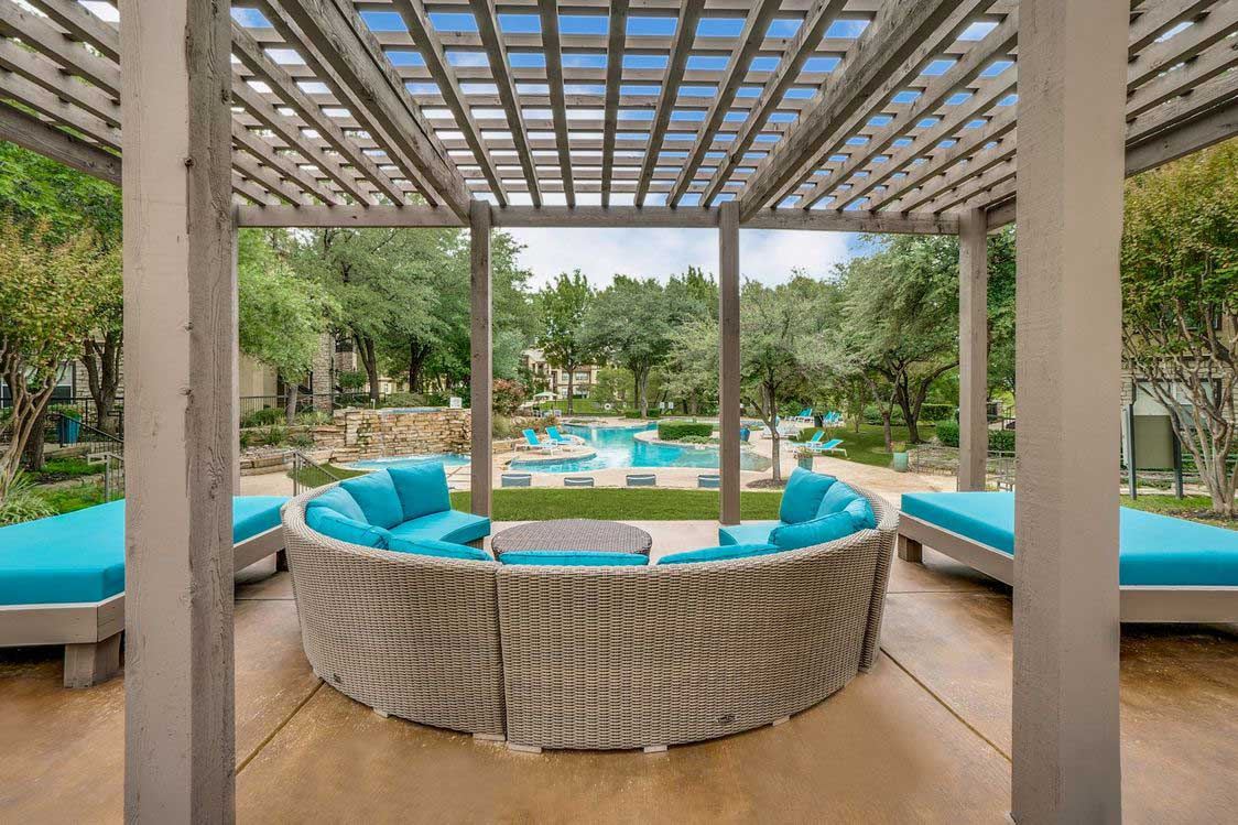 Outdoor Lounge Beside Pool at Hidden Lakes Apartments in Haltom City, Texas