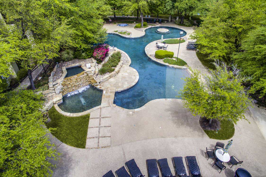Luxury Poolside Amenities with Trees at Hidden Lakes Apartments in Haltom City, Texas