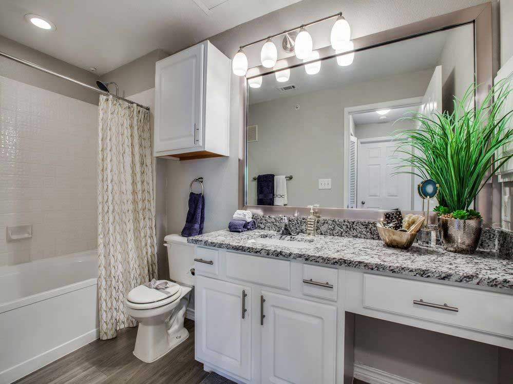 Bathrooms with Granite Vanity at Hidden Lakes Apartments in Haltom City, Texas