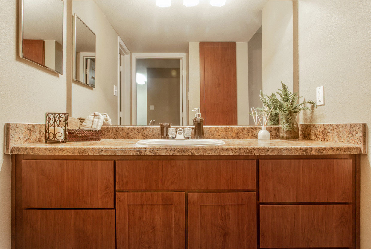 Large Bathroom with a Brown Vanity at at HollyView apartments in Houston, TX