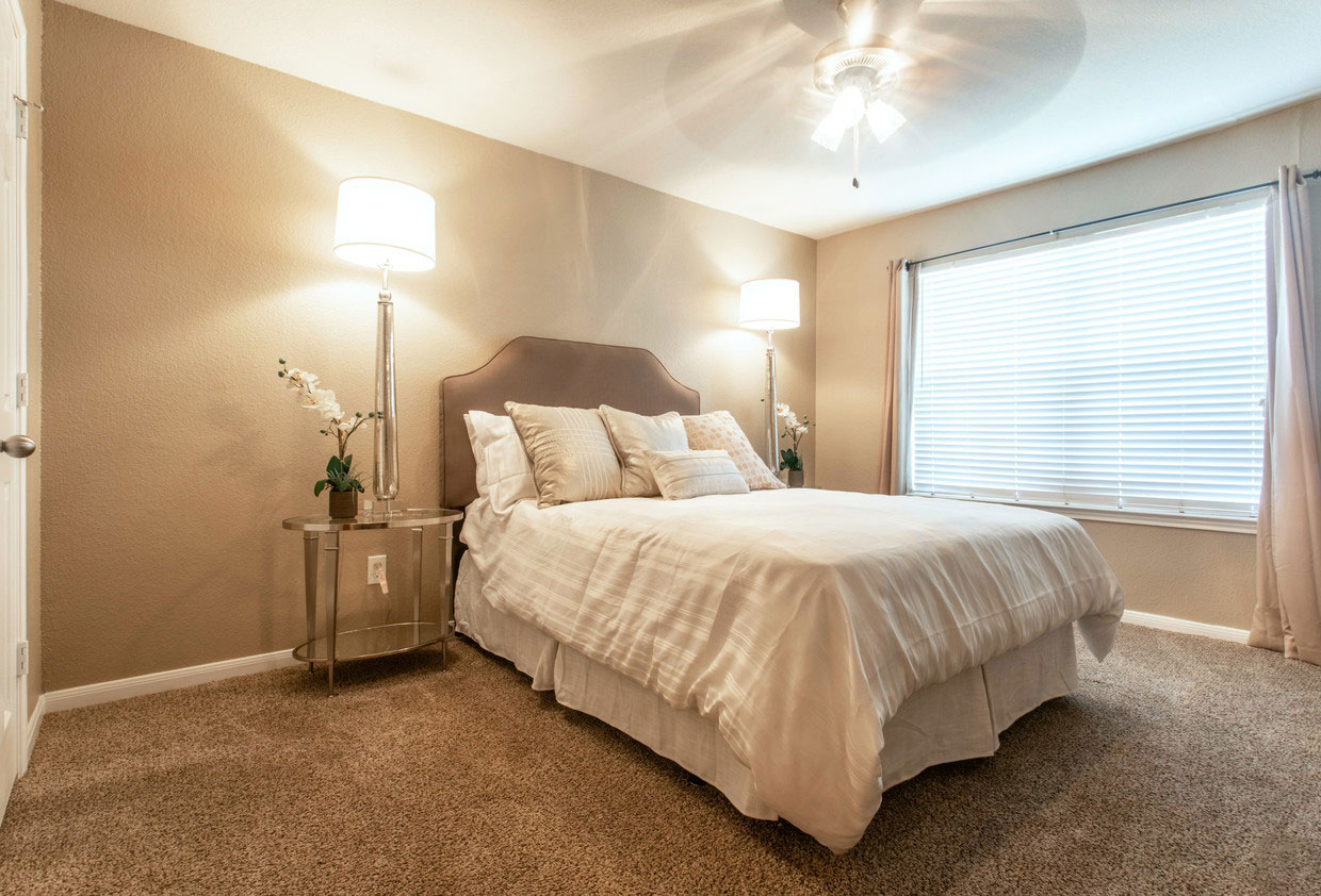 Furnished Bedroom with Carpet Floors and Natural Light at HollyView Apartments in Houston, TX