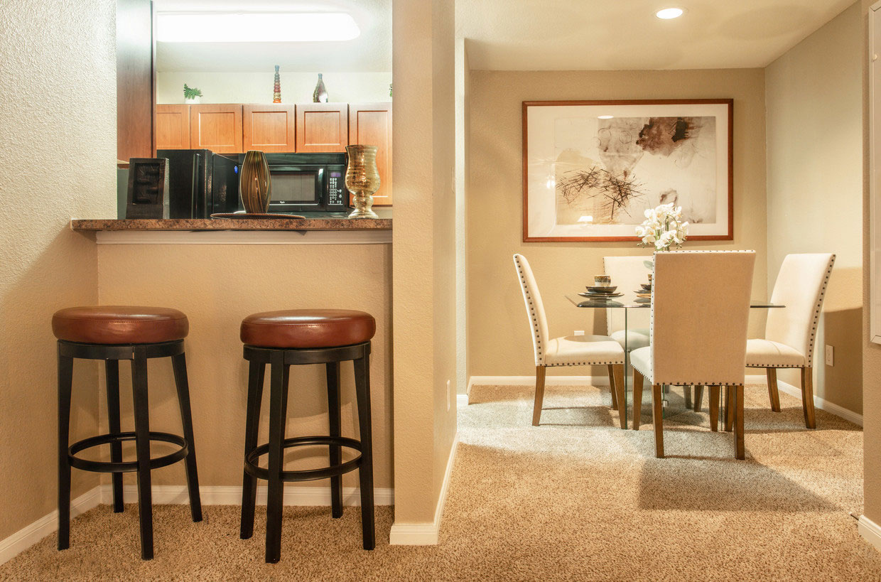 Dining Area with Carpet Flooring and Glass Kitchen Table at HollyView apartments in Houston, TX