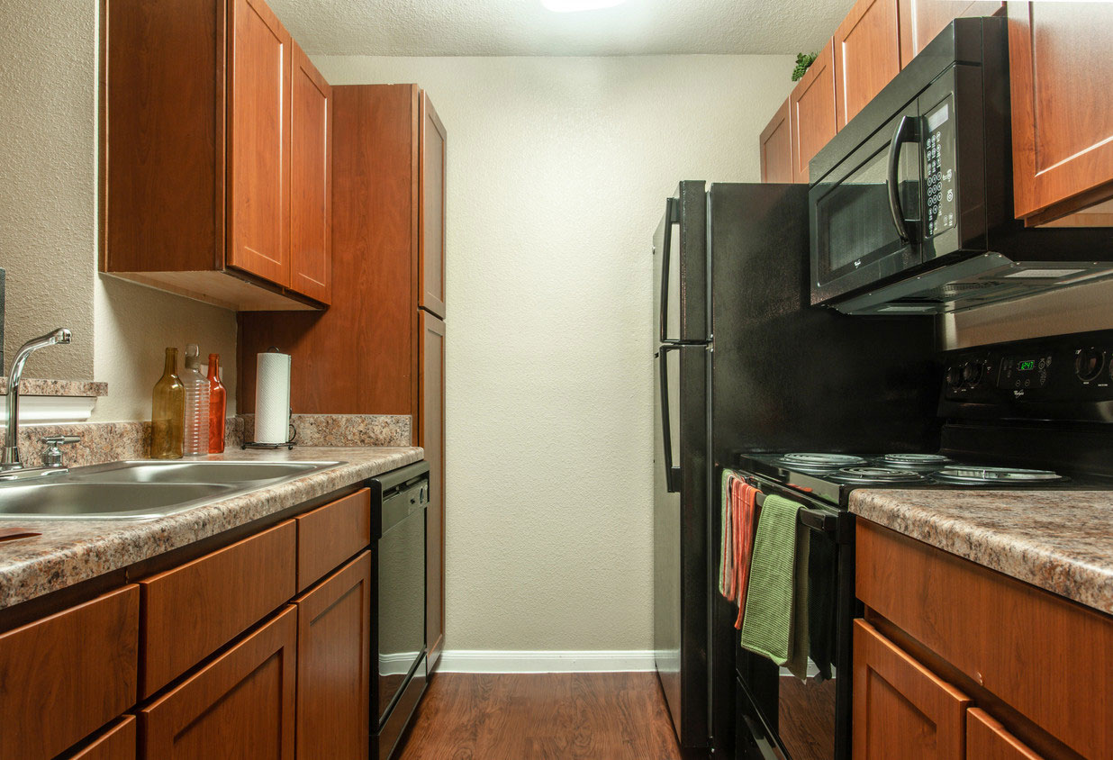 Kitchen with Brown Cabinets and Black Appliances at HollyView apartments in Houston, TX