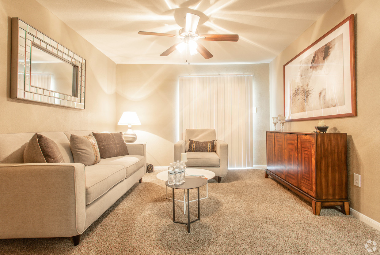 Carpeted living area at Holly View apartments with tan couches