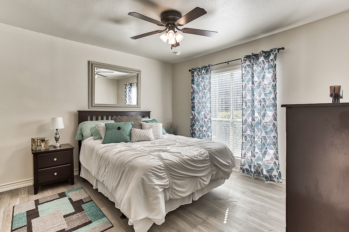Bedroom with Plank Flooring at Indian Run Apartments in Abilene, TX