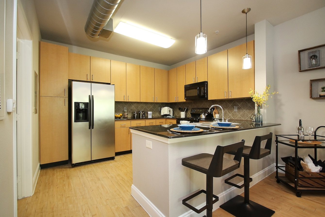 Eat-In Kitchen with Stainless Steel Appliances at King's Cove Apartments in Kingwood, Texas