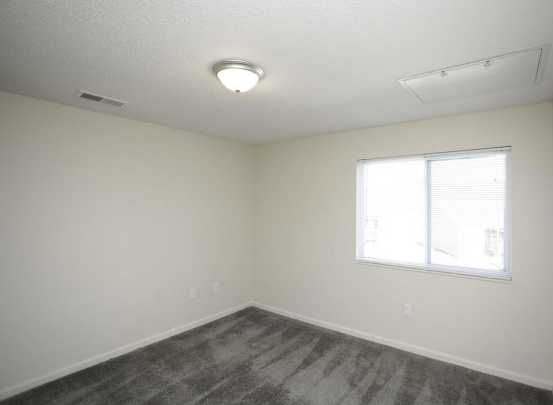 Spacious Bedrooms with Windows at Liberty Heights Apartments in Liberty, MO