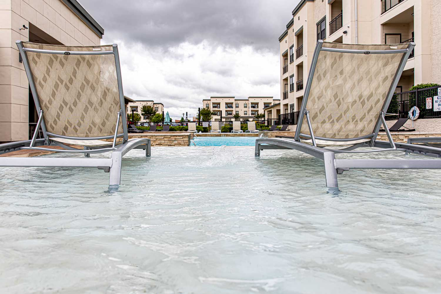 Lounge Chair beside the Pool at Oxford at Crossroads Centre Apartments in Waxahachie, TX