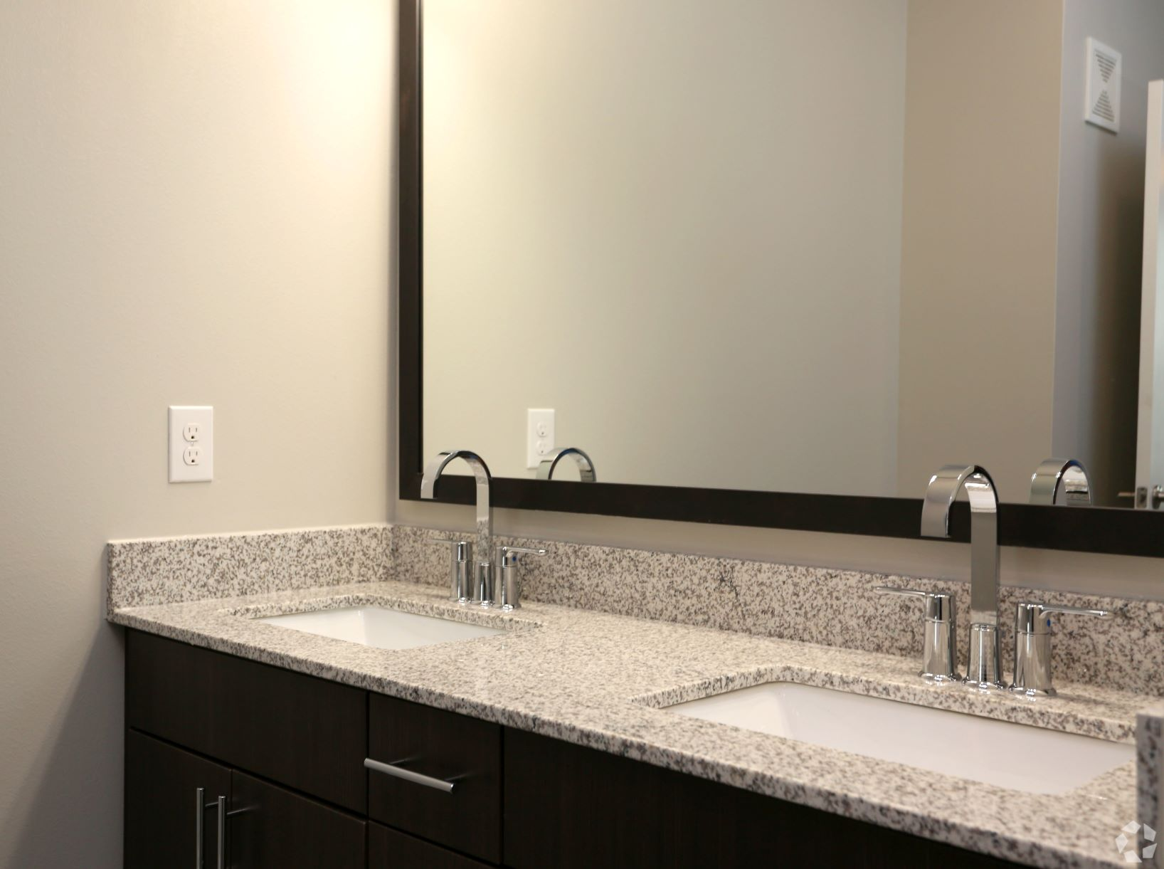 Quartz countertops with elegant framed mirror and walk in shower