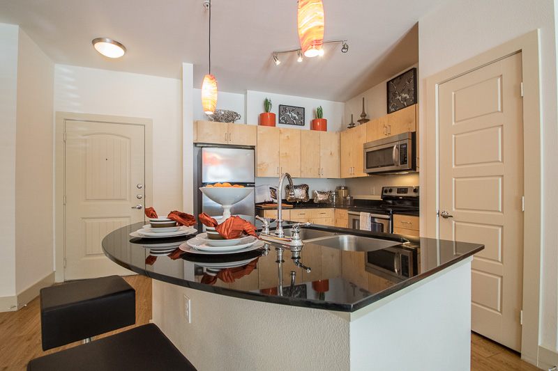 Kitchen with Breakfast Bar at The Oxford at The Boulevard Apartments in Corinth, TX
