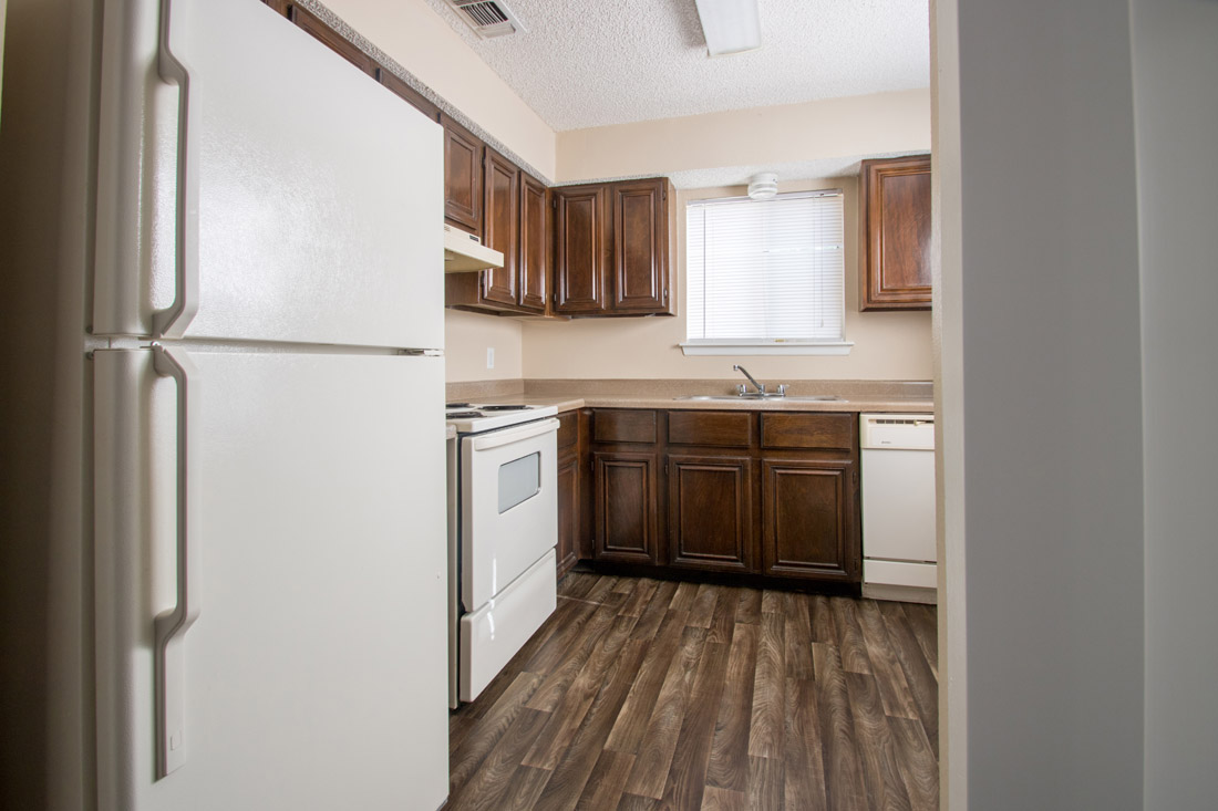 Kitchen with Wood Plank Flooring at Songbird Apartments in San Antonio, Texas