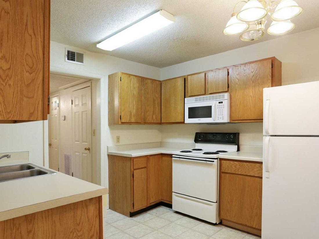 Kitchen with White Appliances at South Creekside Apartments in Fayetteville, AR