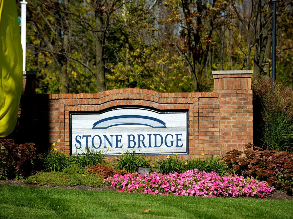 Property Sign Surrounded by Flowers at Stone Bridge Apartments in Mason, Ohio