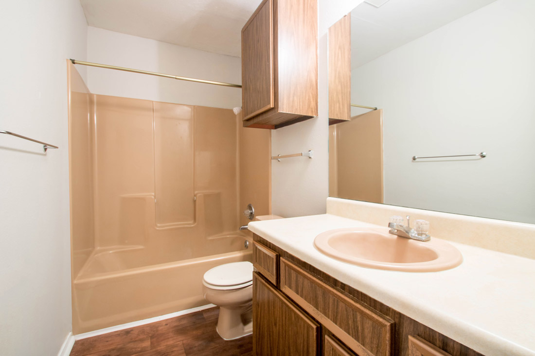 Bathroom with Wood-Look Flooring at The Trace at North Major Apartments in Beaumont, Texas