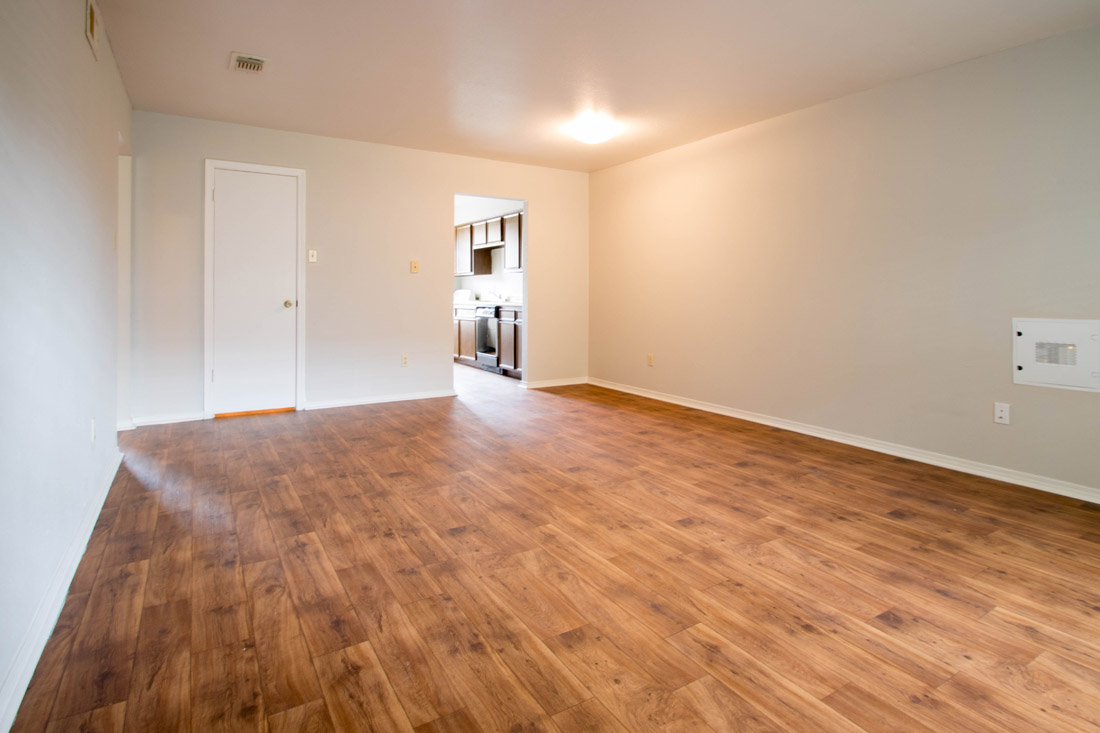Living Room with Wood-Look Flooring at The Trace at North Major Apartments in Beaumont, Texas