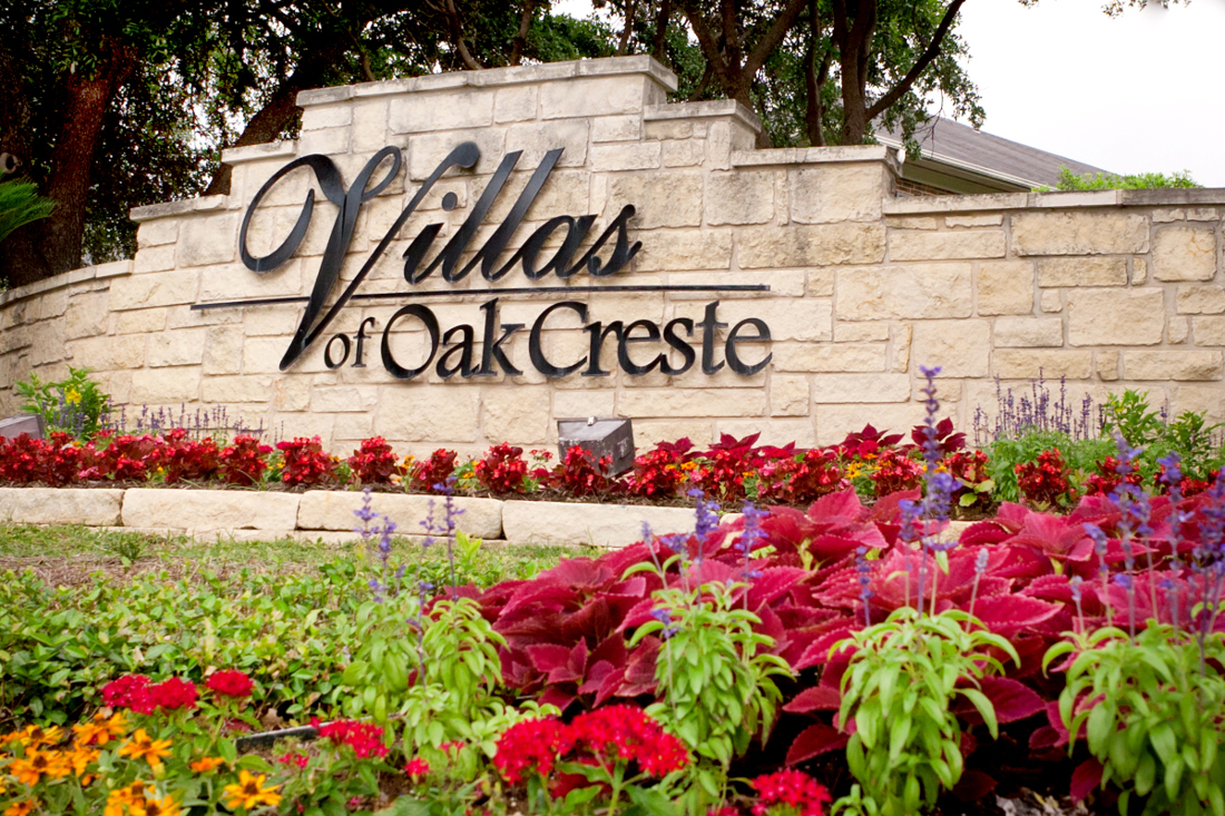 Property Sign with Beautiful Flowers at Villas of Oak Creste Apartments in San Antonio, TX
