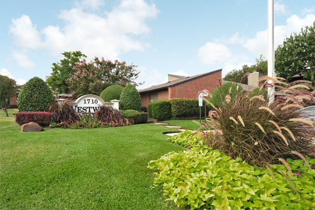 Lush Landscaping with Front Signage at Westwind Apartments in Denton, TX